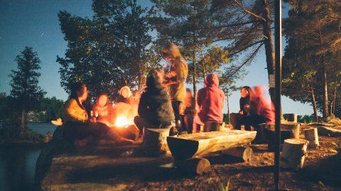 team sitting around campfire team-building