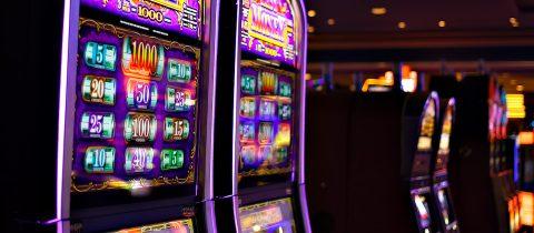 neon slot machines in a row in a dark casino