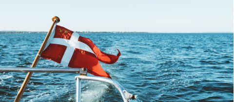 The Danish flag or Dannebrog with a white cross on field of red flies on a boat