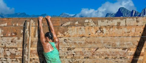 Strong and toned trainer climbing over a wall