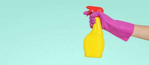 A hand in pink gloves ready to spray some cleaning product